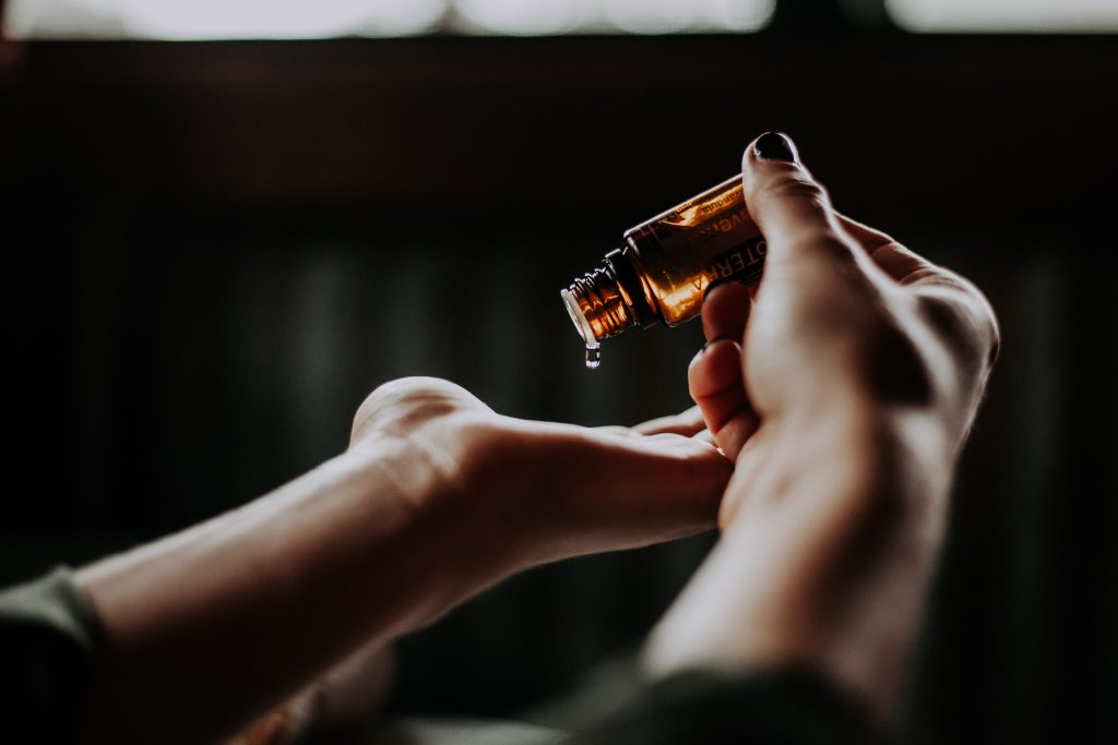 person pouring essential oil