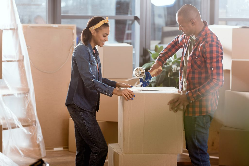 Couple moving box into new apartment