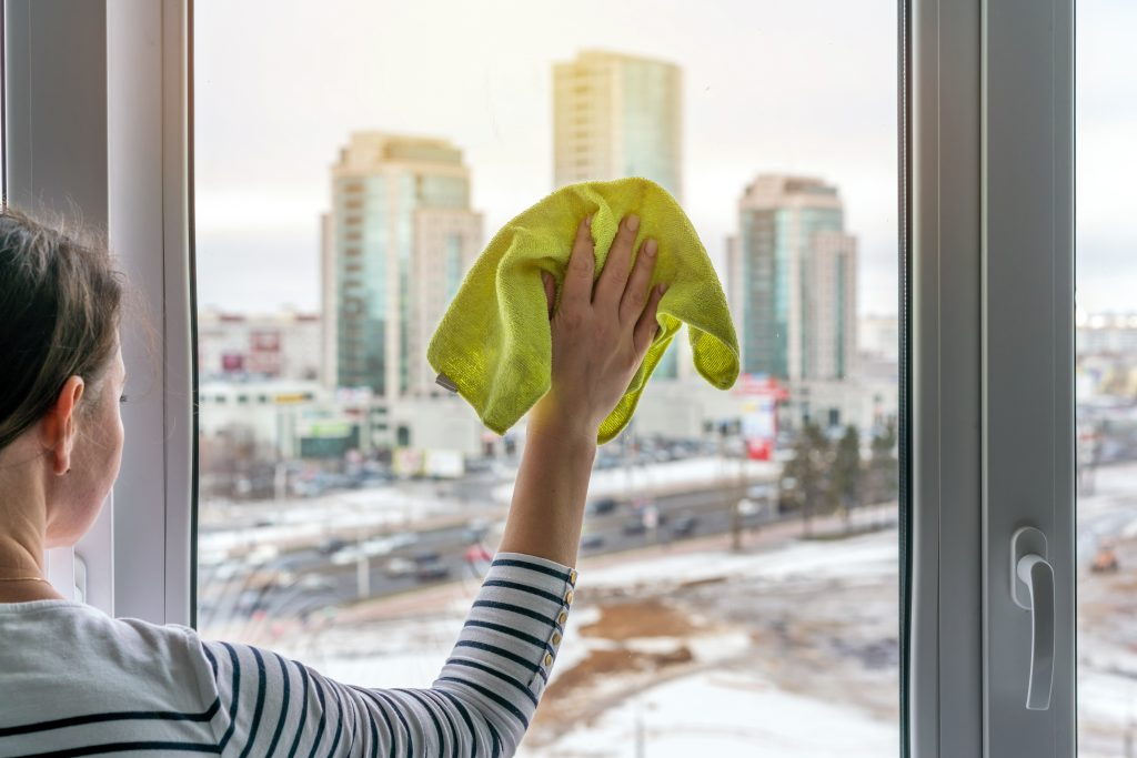 woman washes a window with a green sponge