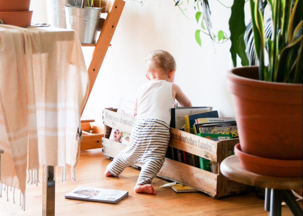 baby rummaging through books in apartment