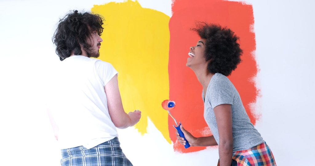 multiethnic couple decorate home by painting interior wall of new house